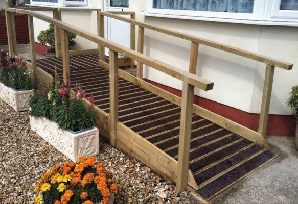 Wood entrance ramp with non-slip surface and handrails.