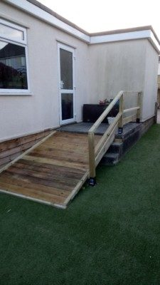 Wood entrance ramp with one handrail.